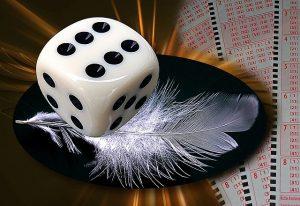un dé posé sur une plume illustrant le hasard pour réussir un concours de nouvelles